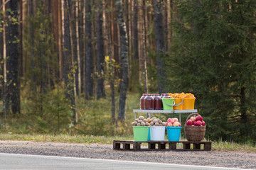 Harvest for sale(potato, mushrooms, apple, different berry) along the road in Russia, pine forest on background. illegal trade on the roads. Organic food