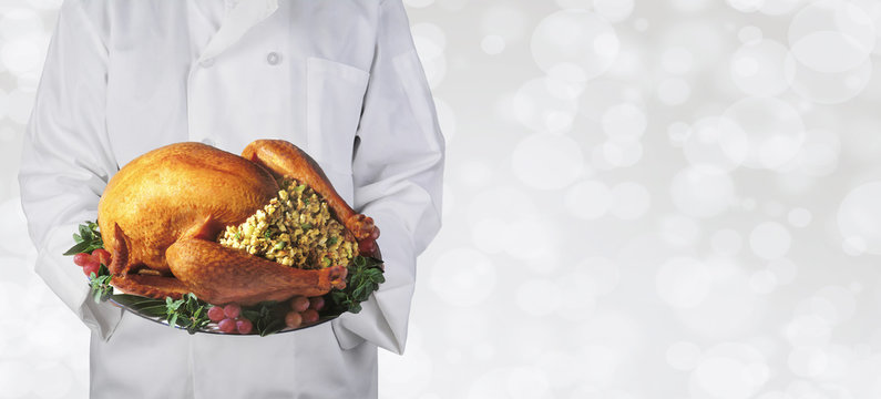 Chef holding a Thanksgiving turkey on a platter