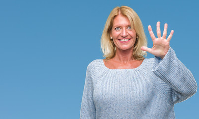 Middle age blonde woman wearing winter sweater over isolated background showing and pointing up with fingers number five while smiling confident and happy.
