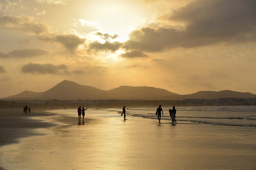silhouettes of people walking along the beach on the background of a pearl sunset