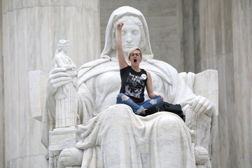 "Protester sits in the lap of ""Lady Justice"" while demonstrators storm the steps and doors of the U.S. Supreme Court as Judge Kavanaugh is sworn in as a justice inside in Washington"
