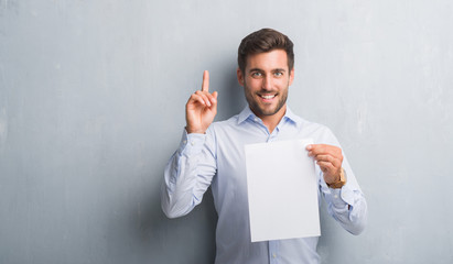 Handsome young man over grey grunge wall holding blank paper sheet contract surprised with an idea or question pointing finger with happy face, number one