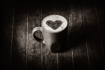cup of coffee with a heart of cinnamon on a wooden table. Image in black and white color style