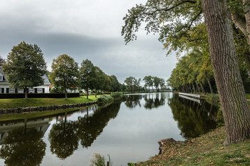 Sluis, Zeeland, Netherlands - September 22, 2018: Gray sky and green bordering trees reflected in quiet water of dead ending canal Bruges-Sluis in Sluis. White house.