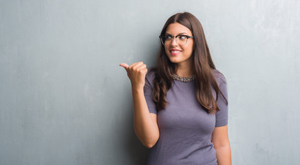 Young brunette woman over grunge grey wall wearing glasses pointing and showing with thumb up to the side with happy face smiling