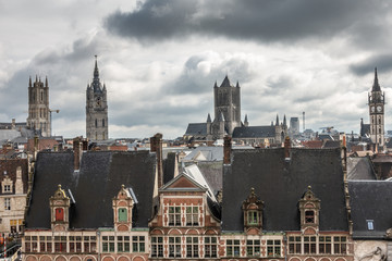 Ghent, Belgium - September 23, 2018: Seen from Gent Castle tower. Four towers: Saint Bavo Cathedral, Belfry, Saint Nicolas church, Postal clock tower. Under heavy cloudscape. Facades Sint Veerleplein.