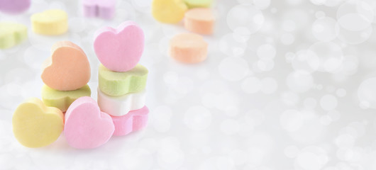 Pastel Candy hearts on a silver bokeh background