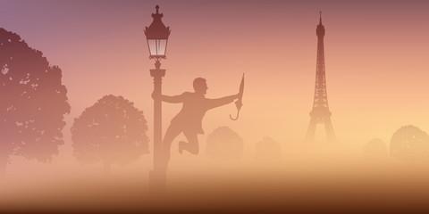 Un homme danse avec un parapluie, autour d'un lampadaire, devant la tour Eiffel à Paris.