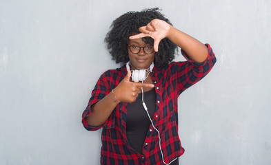 Young african american woman over grey grunge wall wearing headphones smiling making frame with hands and fingers with happy face. Creativity and photography concept.