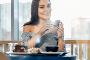 Close up of woman holding cup of coffee, smiling and looking at camera.