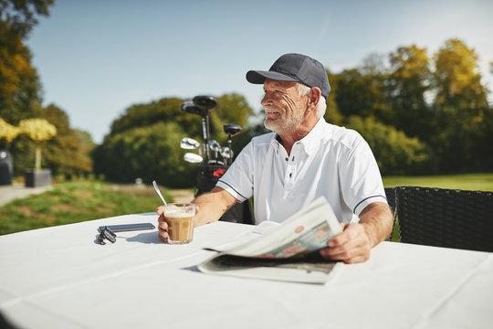 Smiling senior man relaxing at his golf club restaurant