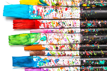 Artistic background. Artist paintbrushes with colourful paint stains isolated on white background