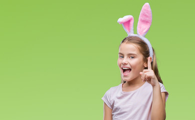 Young beautiful girl wearing easter bunny ears over isolated background pointing finger up with successful idea. Exited and happy. Number one.