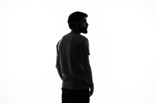 dark silhouette of a young man on a light background