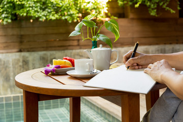Businessman hand writing a note in notebook on wood table with coffee cup and fresh fruit on vacation.