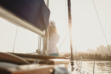 Attractive girl on a yacht at summer day. Close up of fashion portrait of stunning romantic woman posing yacht. Wearing an elegant dress, summer outfit. Blue sky. sunset