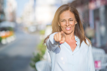 Beautiful middle age hispanic woman at the city street on a sunny day pointing with finger to the camera and to you, hand sign, positive and confident gesture from the front