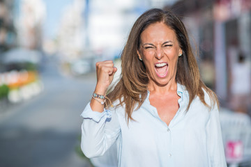 Beautiful middle age hispanic woman at the city street on a sunny day annoyed and frustrated shouting with anger, crazy and yelling with raised hand, anger concept