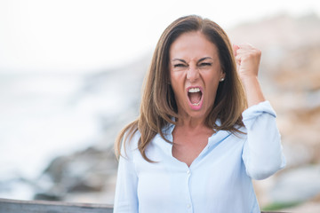Beautiful middle age hispanic woman at the sea shore on a sunny day annoyed and frustrated shouting with anger, crazy and yelling with raised hand, anger concept