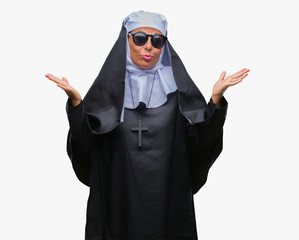 Middle age senior catholic nun woman wearing sunglasses over isolated background clueless and confused expression with arms and hands raised. Doubt concept.
