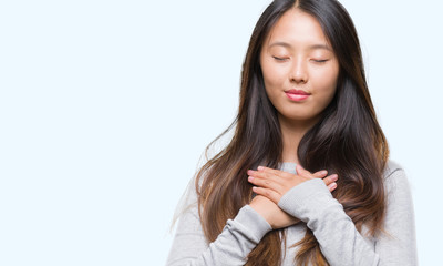 Young asian woman over isolated background smiling with hands on chest with closed eyes and grateful gesture on face. Health concept.