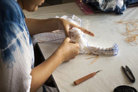 Thai woman people fold bundle and sewing or arashi shibori on fabric at workshop in Nonthaburi, Thailand
