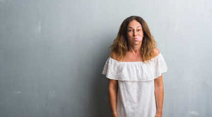 Middle age hispanic woman standing over grey grunge wall puffing cheeks with funny face. Mouth inflated with air, crazy expression.