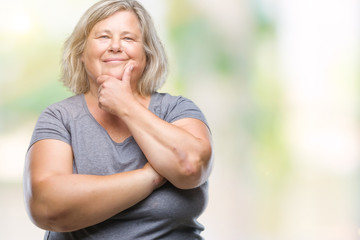 Senior plus size caucasian woman over isolated background looking confident at the camera with smile with crossed arms and hand raised on chin. Thinking positive.