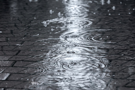 flooded street sidewalk with rippled rain water puddles