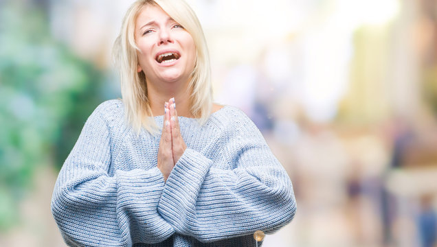 Young beautiful blonde woman wearing winter sweater over isolated background begging and praying with hands together with hope expression on face very emotional and worried. Asking for forgiveness