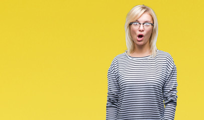 Young beautiful blonde woman wearing glasses over isolated background afraid and shocked with surprise expression, fear and excited face.