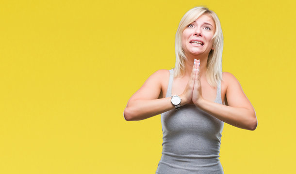 Young beautiful blonde woman over isolated background begging and praying with hands together with hope expression on face very emotional and worried. Asking for forgiveness. Religion concept.