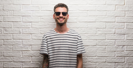 Young adult man wearing sunglasses standing over white brick wall with a happy and cool smile on face. Lucky person.