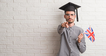 Young adult man over brick wall wearing graduation cap holding uk flag pointing with finger to the camera and to you, hand sign, positive and confident gesture from the front
