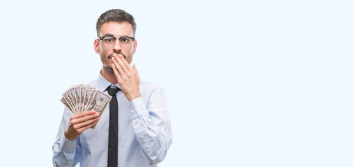 Young hipster business man holding dollars cover mouth with hand shocked with shame for mistake, expression of fear, scared in silence, secret concept