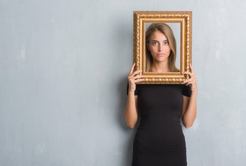 Beautiful young woman over grunge grey wall holding vintage frame with a confident expression on smart face thinking serious