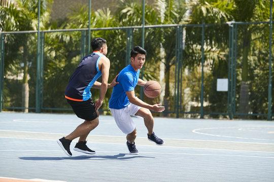 young asiian men playing basketball