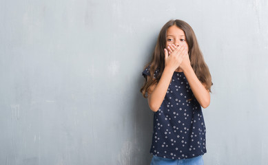 Young hispanic kid over grunge grey wall shocked covering mouth with hands for mistake. Secret concept.