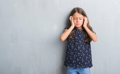 Young hispanic kid over grunge grey wall with hand on head for pain in head because stress. Suffering migraine.
