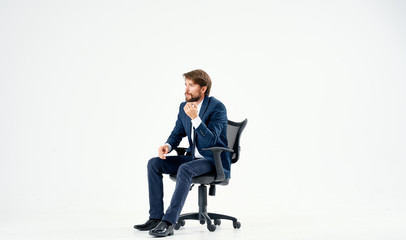 man in a suit sitting in a chair