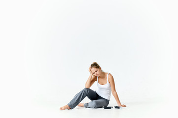 tired woman sitting on the floor next to dumbbells