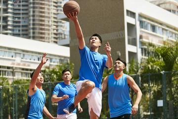 young asian men playing basketball