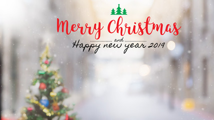 Christmas and Happy new year 2019 on blurred bokeh christmas tree background with snowfall.