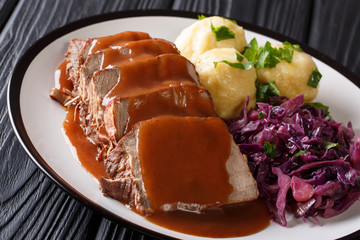Delicious traditional German dinner Sauerbraten - slowly stewed marinated beef with gravy with potato dumplings and red cabbage close-up. horizontal