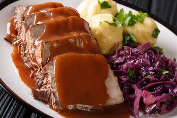 Festive German full dinner Sauerbraten - beef stew with gravy served with potato dumplings and red cabbage close-up. Horizontal