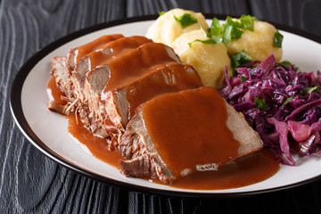 German Sauerbraten is a beef stew with a spicy sauce served with potato dumplings and red cabbage close-up. Horizontal