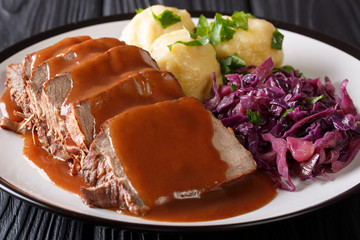 Slow Cooker Pot Roast Sauerbraten with spicy sauce, potato dumplings and red cabbage close-up. horizontal