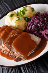 German national dish Sauerbraten served with knodel potato dumplings and red cabbage close-up. vertical