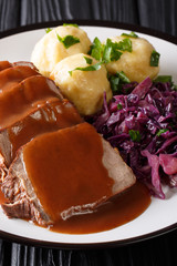 German Slow Cooker Pot Roast (Sauerbraten) with potato dumplings and red cabbage close-up. Vertical