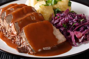 German roast pot Sauerbraten served with potato dumplings and red cabbage close-up. horizontal